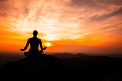Yoga practicioner in sunset - stock photo