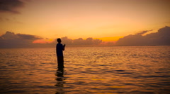 Silhouette of Man worships with head up to the sky and hands in prayer in ocean Stock Footage