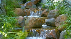 Stock Video Footage of Water Cascades down a Multilevel Garden Waterfall