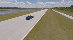 Camera follows Porsche on race track Stock Footage