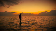 Silhouette of man standing in ocean in prayer during colorful sunrise or sunset Stock Footage