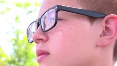 Confident boy looking into distance with cloud reflection in glasses 4k Stock Footage