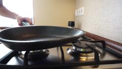 Frying pan being placed on a stove Stock Footage
