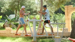 Stock Video Footage of 4k, man and woman playing sports on the training apparatus outdoors