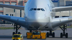 The tractor tows Lufthansa Airbus 380, slow motion Stock Footage