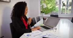 Business woman working on her laptop and talking over the phone early morning Stock Footage