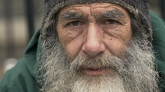 Homeless old man looking in the camera: poor man, beggar man, asking for charity - stock footage