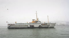 Istanbul ferry sailing into harbor on a snowy winter day Stock Footage