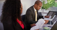 Business people using laptop and reviewing sales figures at desk. Stock Footage