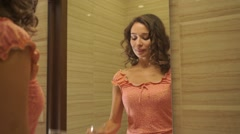 Beautiful girl in a pink dress rinses her mouth in the bathroom Stock Footage