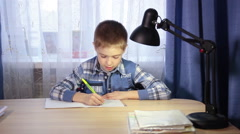 Child doing homework, writing in a notebook in the evening at the table Stock Footage