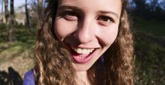 Pretty young woman turns and smiles, distorted by fish eye lens Stock Footage