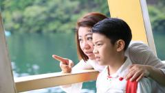 Young asian mother with little son stand on deck of cruise ship . Stock Footage