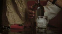 Pouring whiskey to the glass filled with ice cubes. Close up shot. Stock Footage