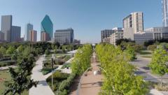 Camera flys Back through arches then up to reveal Dallas Skyline and Park Stock Footage