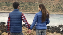 Young couple holding hands, admire view standing on rocks by sea, slow moton Stock Footage