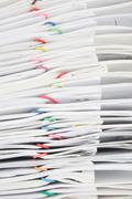 Close up stack paperwork with colorful paper clip overlap report Stock Photos