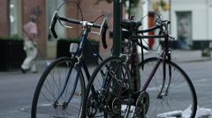 Stock Video Footage of old man sweeping his storefront bicycles chained to parking sign pole SoHo 4K
