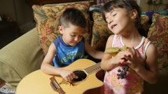 CUTE KIDS PLAY GUITAR AND SING SLOW MOTION Stock Footage