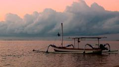 An outrigger fishing boat in Bali calmly floats during sunrise Stock Footage