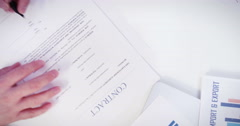 High angle shot of two business partners signing a contract and shaking hands. Stock Footage