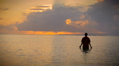 Man stands in the ocean with rays of light coming in and his palms open Stock Footage