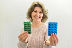 Adult woman holding  blister pack of a pills Stock Photos