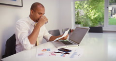 A stressed businessman having a video call on a mobile phone while using laptop. - stock footage