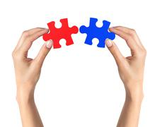 Red and blue puzzle in woman hands isolated on white background - stock photo