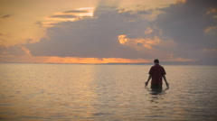 Man walks out of the ocean during a sunset with rays of light coming in Stock Footage