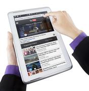 Businessperson hand opens youtube on tablet - stock photo
