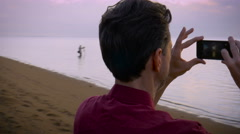 Hand held shot of a middle aged man taking smart phone photos on the beach Stock Footage