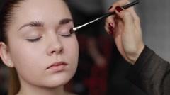 Professional make-up artist applying shadows on eyelid. Close-up Stock Footage