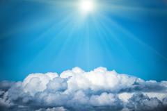 White clouds and bright sun on the blue sky Stock Photos