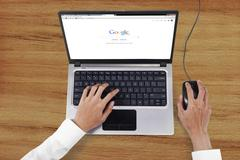 Hands opens google search web page - stock photo