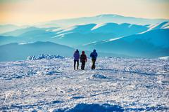 People walking at sunset in winter mountains - stock photo