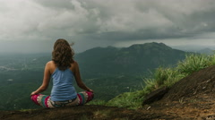 Fit girl doing yoga meditation on top of mountain in tropics Stock Footage