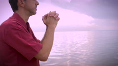 Worried man on beach prays for answers push in shot handheld Stock Footage