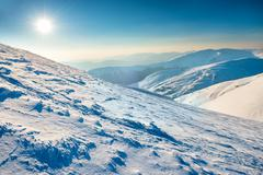 Stock Photo of Bright sun in winter mountains
