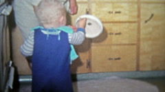 1968: Toddler boy playing with pots in kitchen cabinets. - stock footage