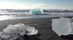 Icebergs on the beach and sea surf in the background Stock Footage