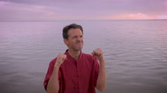 A man celebrates having it all by clentching his fists and smiling on the beach Stock Footage