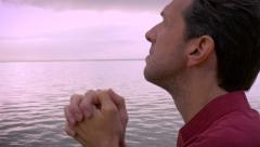 Handheld push in of man praying and looking up to the sky Stock Footage