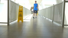 Man walking down walkway with slippery when wet sign Stock Footage