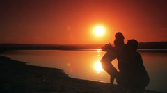 Two boys ran to a happy mother and held her on the beach at sunset silhouette of Stock Footage