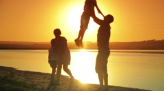 Happy young family to run and play on the beach at sunset summer warm evening - stock footage