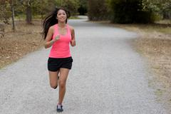 Fit young woman jogging on a country road Stock Photos