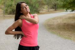 Young woman out jogging suffers a muscle injury Stock Photos