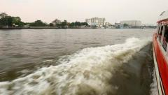 Bangkok riverside from quickly running express boat, white wake on water Stock Footage