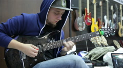 A visitor musical salon testing a new electric guitar. Stock Footage